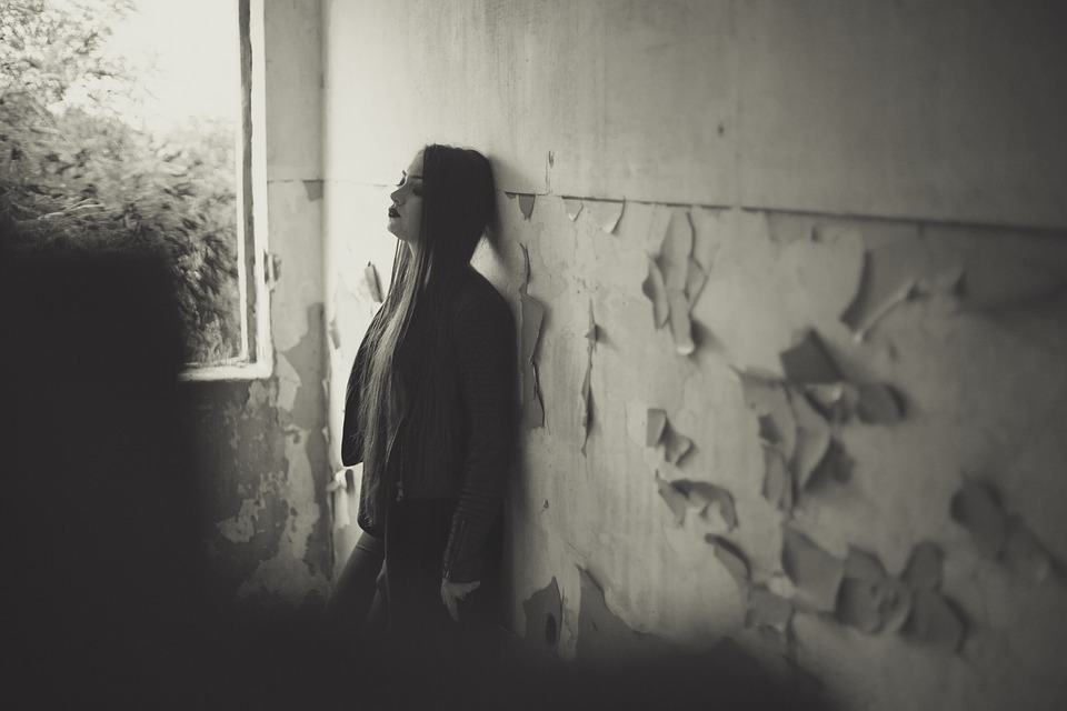 goth woman leans against wall of what looks like an abandoned building