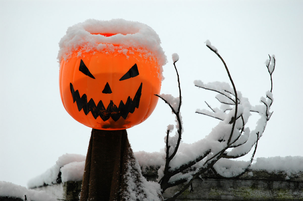 Plastic pumpkin sits atop snowy fence post