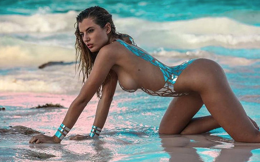 model wearing shiny tape swimsuit at the beach