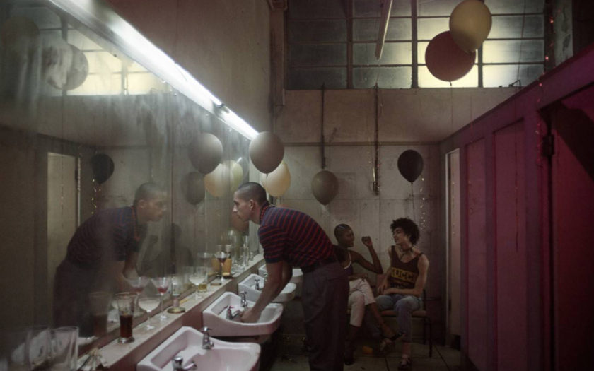people lounge in a 1983 night club bathroom that is full of balloons and half empty drink glasses