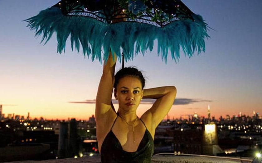 woman holding led festival umbrella against the LA skyline