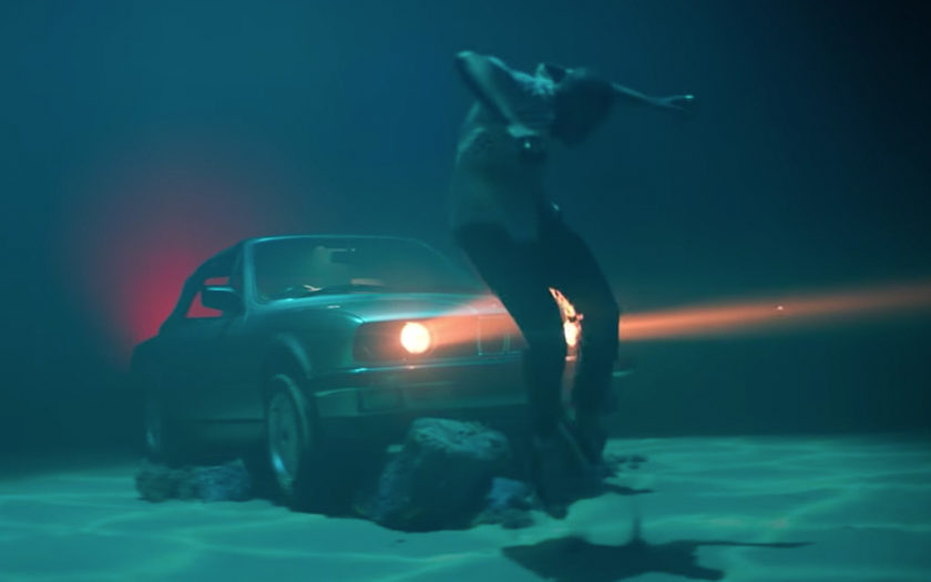 screenshot from go deep music video of man dancing underwater in front of a car with the headlights on