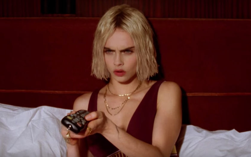 Cara Delevingne mean mugs the television in a hotel room