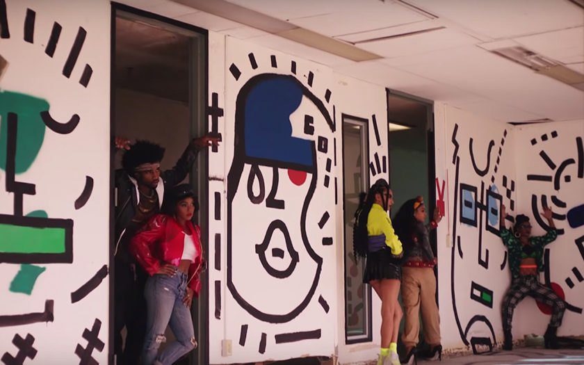 screenshot from screwed music video in an abandoned building with murals on the walls